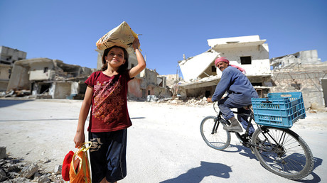 A girl is seen at a damaged site in Aleppo's Sheikh Maqsoud neighbourhood, Syria. © Omar Sanadiki
