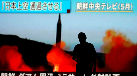 A man walks in front of a monitor showing news of North Korea's fresh threat in Tokyo, Japan. © Toru Hanai