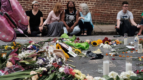 Women sit by an impromptu memorial of flowers commemorating the victims at the scene of the car attack, Charlottesville, Virginia, August 14, 2017. © Justin Ide