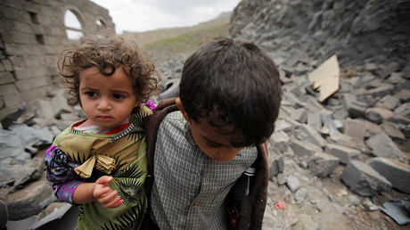 FILE PHOTO: A boy carries his sister, as he walks on rubble of a houseafter it was destroyed by a Saudi-led air strike in Yemen's capital Sanaa © Mohamed Al-Sayaghi