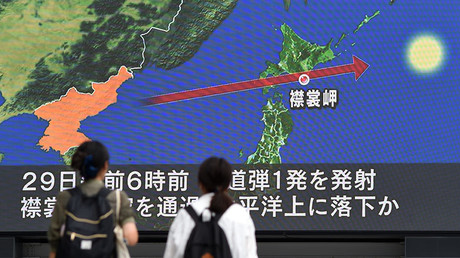 Pedestrians watch the news on a huge screen displaying a map of Japan (R) and the Korean Peninsula, in Tokyo on August 29, 2017. © Toshifumi Kitamura