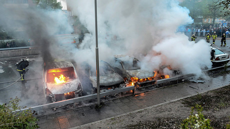 FILE PHOTO: Firemen extinguish a row of burning cars in the suburb of Rinkeby, Sweden © Fredrik Sandberg