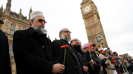 Muslim men stand in line on Westminster Bridge during an event to mark one week since a man drove his car into pedestrians then stabbed a police officer in London, Britain, March 29, 2017. © Stefan Wermuth