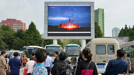 North Koreans watch a news report showing North Korea's Hwasong-12 intermediate-range ballistic missile launch on electronic screen at Pyongyang station in Pyongyang, North Korea August 30, 2017 © Kyodo