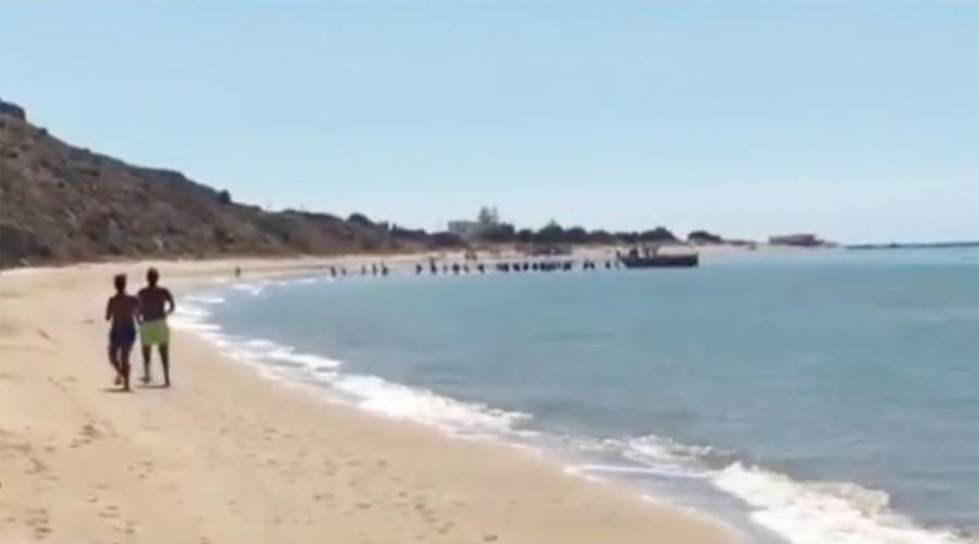 Migrants rush across Sicilian beach after dramatic boat landing (VIDEO)