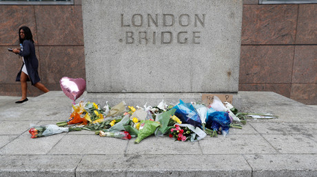 A woman passes flowers left on the south side of London Bridge near Borough Market after an attack left 7 people dead and dozens of injured in London, Britain, June 5, 2017 © Peter Nicholls