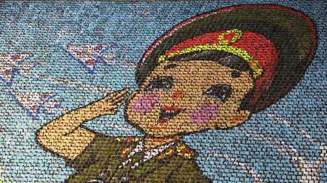 North Korean students use different colored cardboard to form a picture of a child  in uniform, Pyongyang © Jason Lee