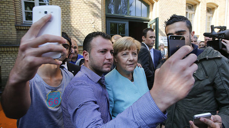 Migrants from Syria and Iraq take selfies with German Chancellor Angela Merkel outside a refugee camp near the Federal Office for Migration and Refugees after their registration at Berlin's Spandau district, Germany, September 10, 2015. © Fabrizio Bensch
