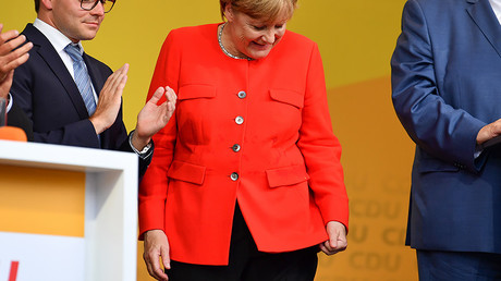 German Chancellor Angela Merkel looks at a stain on her jacket during a campaign event at the University Square in Heidelberg, Germany, 5 September 2017. © Uwe Anspach / dpa / Global Look Press