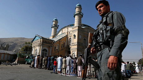 A policeman stands guard as men perform prayers in Kabul, Afghanistan © Mohammad Ismail
