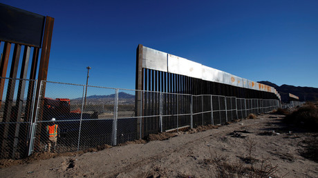 A worker stands next to a newly built section of the U.S.-Mexico border © Jose Luis Gonzalez