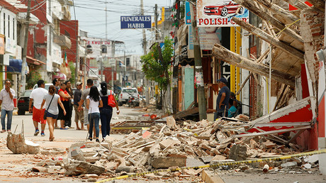 Residents walk past a building destroyed in an earthquake that struck off the southern coast of Mexico, in Juchitan, Mexico September 8, 2017. © Jorge Luis Plata