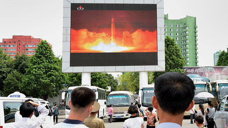 FILE PHOTO: People watch news report showing North Korea's Hwasong-14 missile launch on electronic screen at Pyongyang station, North Korea. © Kyodo