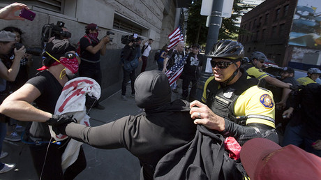 Police try to contain Antifa protesters from approaching members of the Patriot Prayer Movement during a protest to oppose the right wing group
