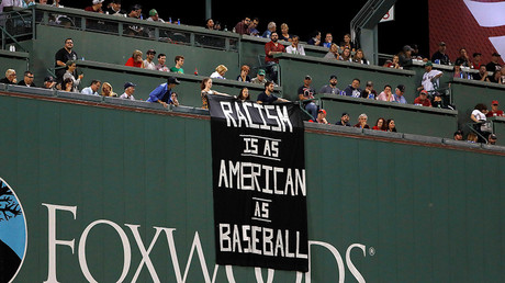 Fans on top of the Green Monster display a racism sign between the top and bottom of the fourth inning during a game between the Boston Red Sox and the Oakland Athletics at Fenway Park. © Winslow Townson / USA  Today / Sports