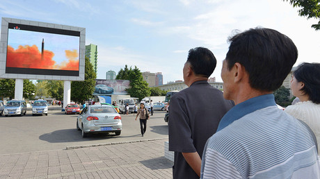 North Korean watch news report showing North Korea's Hwasong-12 intermediate-range ballistic missile launch on electronic screen in Pyongyang © Kyodo