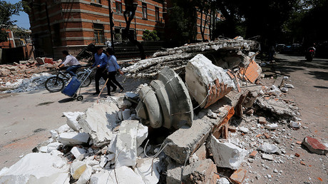 People walk next to debris after an earthquake in Mexico City, Mexico September 19, 2017. © Claudia Daut