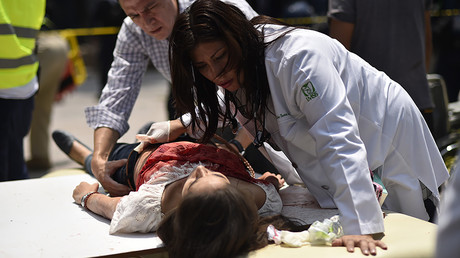 An injured woman is helped after a powerful quake in Mexico City on September 19, 2017. © Pedro Pardo / AFP