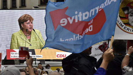 German's right-wing Alternative for Germany (AfD)'s supporter waves an AfD's flag in front of a screen featuring German Chancellor Angela Merkel's speech during her electoral meeting  © John MacDougall