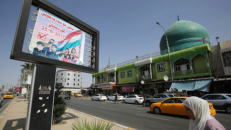 Iraqis drive past a billboard encouraging people to vote in the upcoming independence referendum for the Kurdistan region on September 24, 2017, in central Kirkuk. ©