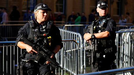 Armed police officers stand near one of the entrances to the Manchester Arena in Manchester © Phil Noble
