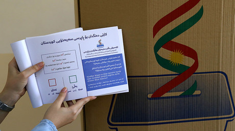 An employee from the Independent High Electoral Referendum Commission holds a voting ballot book at a voting station, in Arbil, the capital of the autonomous Kurdish region of northern Iraq, on September 24, 2017. © Safin Hamed / AFP