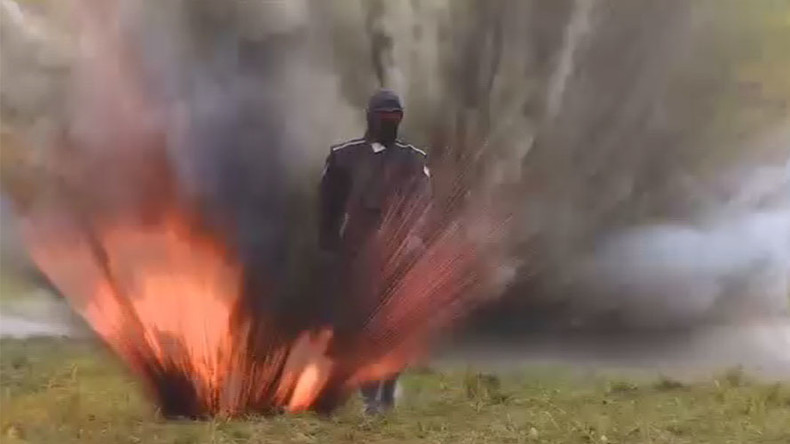 Russian woman casually walks through explosions & fire to test armor suit (VIDEO)