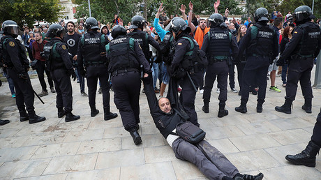 A man is dragged away, after scuffles broke out with Spanish Civil Guard officers, outside a polling station for the banned independence referendum in Sant Julia de Ramis, Spain October 1, 2017. © Albert Gea