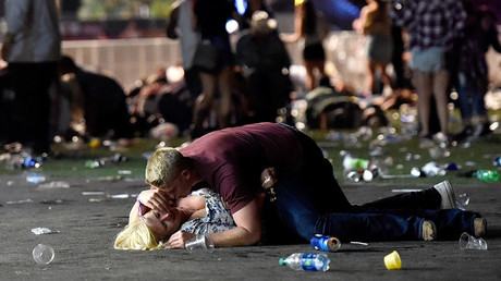 A man lays on top of a woman as others flee the Route 91 Harvest country music festival grounds after a active shooter was reported on October 1, 2017 in Las Vegas, Nevada. © David Becker / Getty Images
