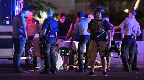 Police officers stand by as medical personnel tend to a person on Tropicana Ave. near Las Vegas Boulevard after a mass shooting at a country music festival nearby on October 2, 2017 in Las Vegas, Nevada. © Ethan Miller / Getty Images