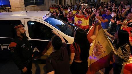 A Catalan regional police officer looks on as people who showed up to support the Spanish national police officers staying in town, hold up Spanish flags as police vehicles depart in Pineda de Mar, north of Barcelona, Spain, October 3, 2017. © Albert Gea