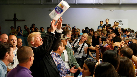 U.S. President Donald Trump tosses rolls of paper towels to people at a hurricane relief distribution center at Calvary Chapel in San Juan, Puerto Rico, October 3, 2017. © Jonathan Ernst