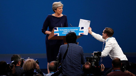 A member of the audience hands a P45 form (termination of employment tax form) to Britain's Prime Minister Theresa May as she addresses the Conservative Party conference in Manchester, October 4, 2017. Phil Noble © Reuters