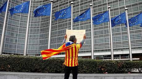 Catalan Raimon Castellvi, wearing a flag with an Estelada (Catalan separatist flag), holds a sign as he protests outside the European Commission in Brussels after Sunday's independence referendum in Catalonia, Belgium October 2, 2017. © Francois Lenoir