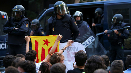 A protestor holds up an Estelada (Catalan independence flag) in front of a line of Spanish national police who surrounded the leftist Popular Unity Candidacy (CUP) party headquarters in Barcelona, Spain, September 20, 2017 © Albert Gea