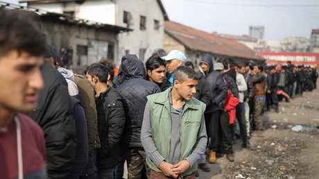 FILE PHOTO: Migrants stand in line to receive free food outside a derelict customs warehouse in Belgrade © Marko Djurica