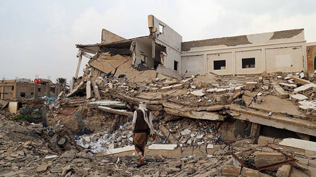 A Yemeni man walks past a destroyed school building on March 16, 2017, that was damaged in an air strike in the southern Yemeni city of Taez. © Ahmad Al-Basha
