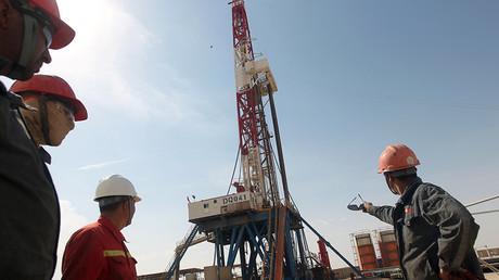 Gazprom employees near a drilling platform for Gazprom company at an oilfield in Badra, Iraq © AFP