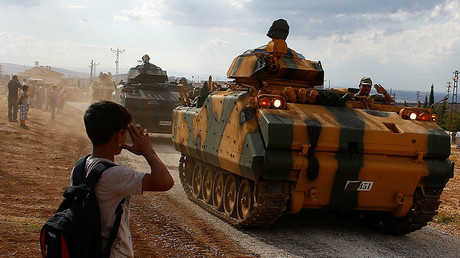 A boy salutes as Turkish Armed Forces vehicles drive pass by a village on the Turkish-Syrian border line in Reyhanli, Hatay province, Turkey October 11, 2017 © Osman Orsal