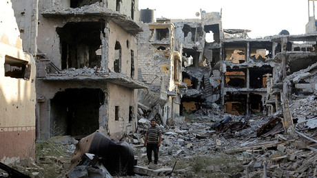 A man stands next to destroyed and damaged buildings in Sabri, a central Benghazi district, Libya © Esam Omran Al-Fetori