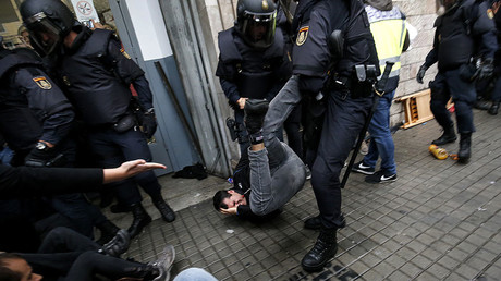 Spanish police officers drag a man as they try to disperse voters arriving to a polling station in Barcelona, on October 1, 2017 © Pau Barrena