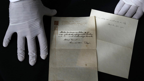 A picture taken on October 19, 2017, shows Gal Wiener, owner and manager of the Winner's auction house in Jerusalem, displays two notes written by Albert Einstein, in 1922, on hotel stationary from the Imperial Hotel in Tokyo Japan. © Menahem Kahana