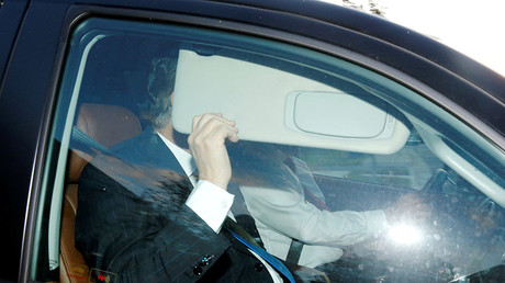 Paul Manafort hides behind his car visor as he leaves his home in Alexandria, Virginia, U.S. October 30, 2017. © Jonathan Ernst