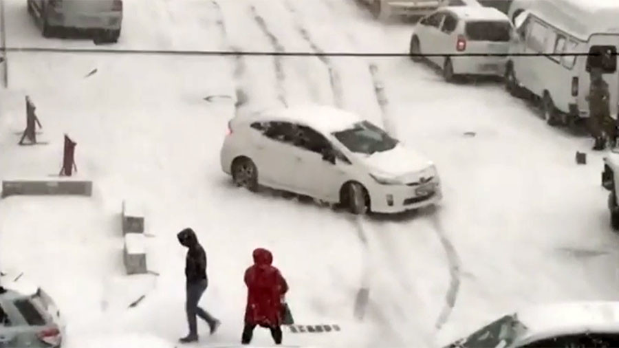 Skid row! Cars slide down slippery slope, slamming into others after heavy snowfall (VIDEO)
