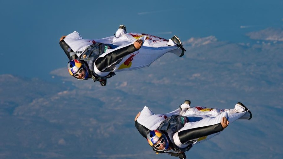 Wingsuit flyers jump off mountain & into moving plane in insane stunt (VIDEO)