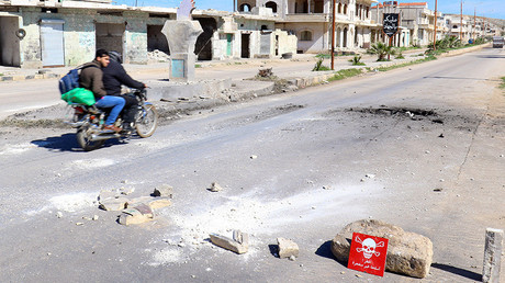 FILE PHOTO: Men ride a motorbike past a hazard sign at a site of an alleged chemical attack in the town of Khan Sheikhoun in Idlib, Syria April 5, 2017. © Ammar Abdullah