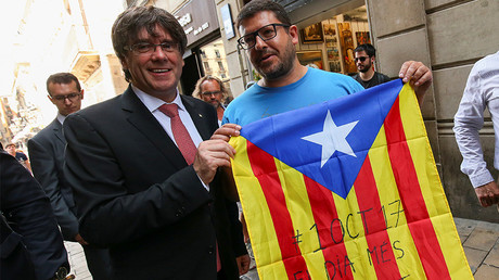Carles Puigdemont poses next to a pro-independence supporter with a Catalan Estelada flag © Albert Gea
