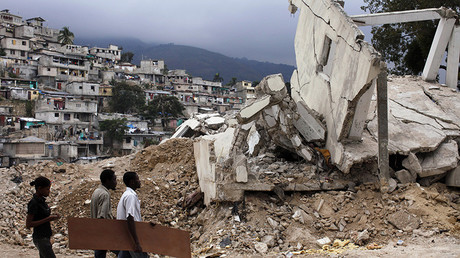 FILE PHOTO Haitians walk next to a building destroyed by the January 2010 earthquake in Port-au-Prince January 7, 2011 © Eduardo Munoz