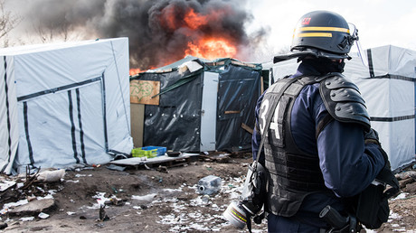 FILE PHOTO: A French riot police stands near a makeshift accommodation that is on fire during the dismantling of the southern part of the so-called 'Jungle' migrant camp in Calais, northern France © Denis Charlet