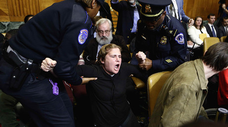 Protesters are carried away by police as they disrupt the US Senate Budget Committee meeting in Washington, DC, November 28, 2017 © Joshua Roberts